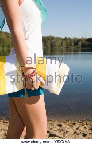 Woman carrying a towel near a lake - Stock Photo