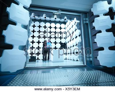 Engineers reviewing test results in laboratory in an anechoic chamber used for electromagnetic compatibility testing of electrical and electronic equipment - Stock Photo