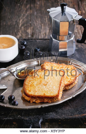 Breakfast theme. Grilled Toasts with honey, blueberries, cup of coffee espresso and coffee pot, served on vintage tray over old - Stock Photo