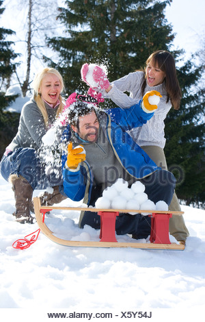 Two young women throwing snowballs on young man sitting by sled in snow, laughing - Stock Photo