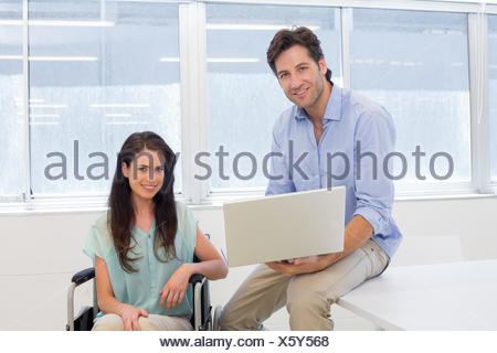 Businessman with laptop and businesswoman in wheelchair - Stock Photo