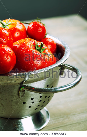 fresh tomatoes (in metal colander) and herbs on a wooden table - Stock Photo