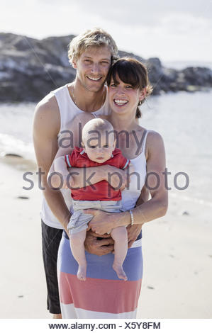 A family day out on the beach. Two people and a baby. - Stock Photo