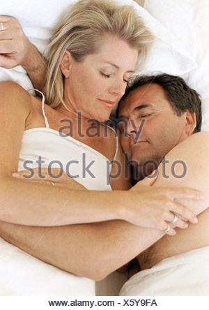 Couple in bed sleeping, in each other's arms - Stock Photo