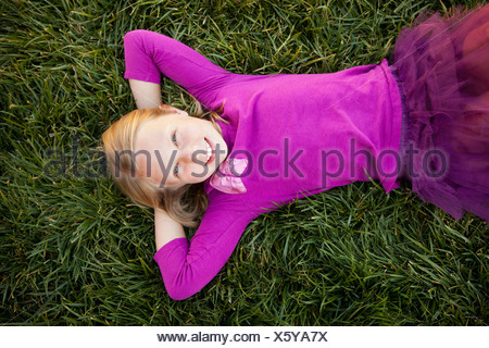 A young girl lying on her back on grass her hands behind her head smiling looking camera View from above - Stock Photo