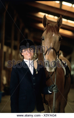 Portrait of a female jockey standing with a horse - Stock Photo