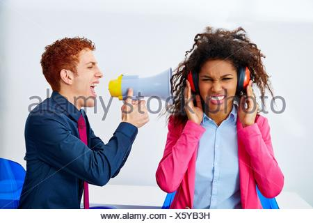 businessman shouting in megaphone to african executive with scared expression. - Stock Photo