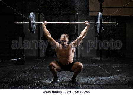 Bare chested young man weightlifting barbell in dark gym - Stock Photo
