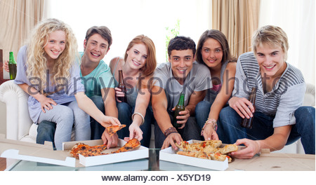 Friends eating pizza at home - Stock Photo