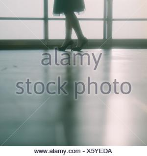 Low Section Of Woman In High Heels Standing Against Window - Stock Photo