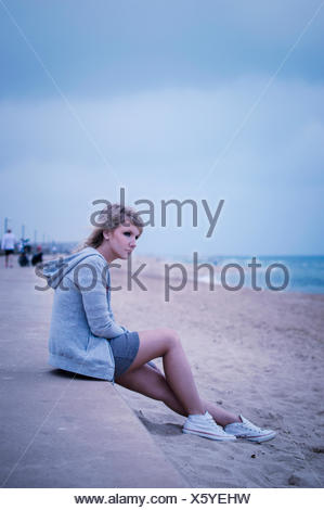 Young woman sitting on sea wall, looking out to sea - Stock Photo