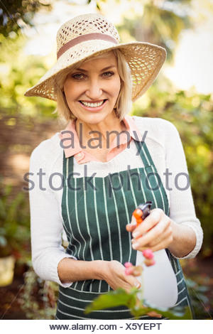 Woman smiling while watering plants