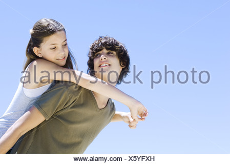 Teen boy carrying younger sister on his back, both smiling at each other, low angle view - Stock Photo