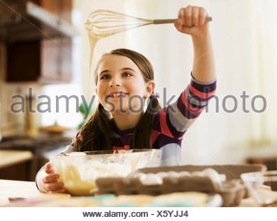 Girl mixing cake batter in bowl - Stock Photo
