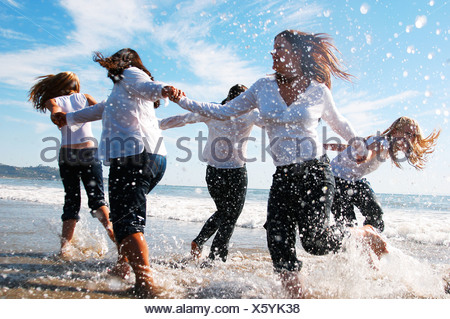 Girls holding hands and splashing water - Stock Photo