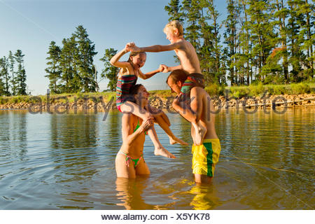 Happy couple with children on shoulders, having water fight in lake - Stock Photo