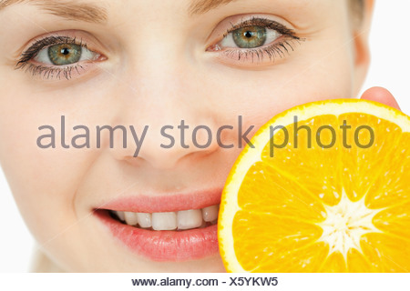 Close up of a woman placing an orange near her lips - Stock Photo