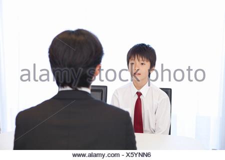 Junior High School Boy Talking to Teacher - Stock Photo