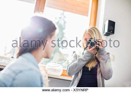 Teenage girl photographing friend with camera - Stock Photo