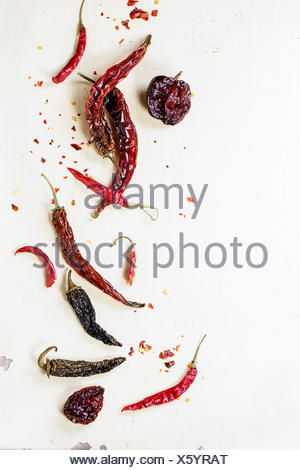 Assortment of dryed red hot chili peppers over white wooden background - Stock Photo