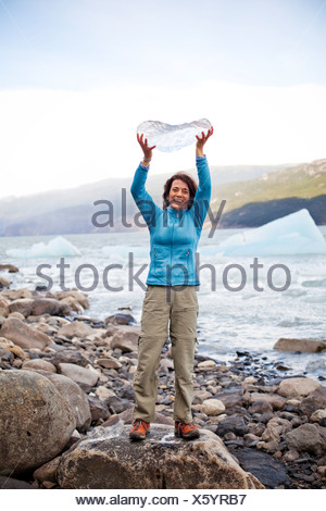 A smiling woman holds a piece of ice, which fell from a glacier, while standing on the rocky shore. - Stock Photo