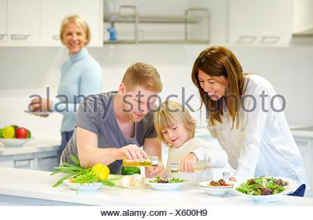 Family in the kitchen. Three generations. Healthy eating. Healthy growth. Making vegetable salad. - Stock Photo