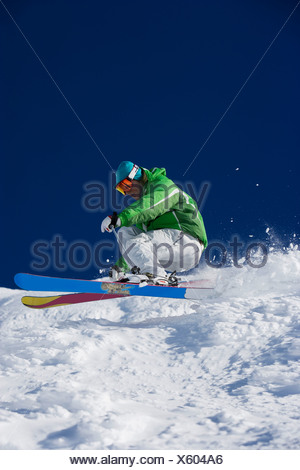 Man in green carving downhill. - Stock Photo