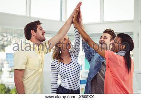 Happy creative team giving a motivational gesture - Stock Photo