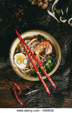 Ceramic bowl of asian ramen soup with shrimp, noodles, onion, sliced egg and mushrooms, served with red chopsticks and chili pep - Stock Photo