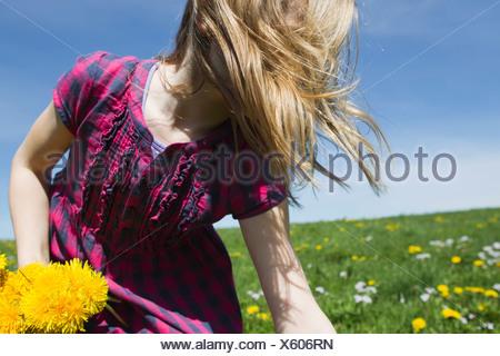 Girl picking wildflowers in field - Stock Photo