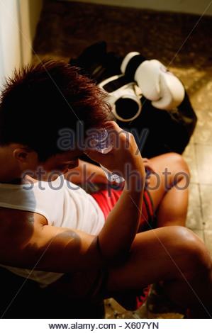 Man sitting down, hand on head - Stock Photo