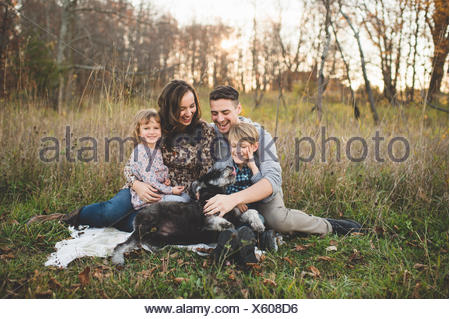 Portrait of young couple with son, daughter and dog in field - Stock Photo