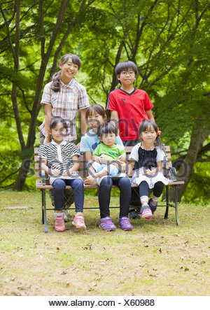 Siblings in a big family sitting on a bench - Stock Photo