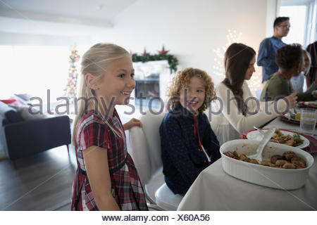 Brother and sister enjoying family Christmas dinner at table - Stock Photo