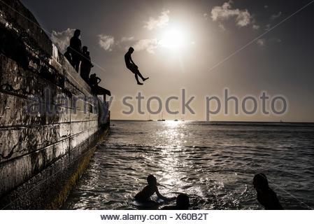 Teenagers dive off Kuhio Pier. - Stock Photo