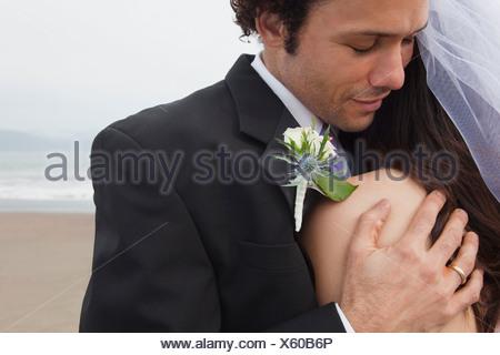 USA, California, San Francisco, Baker Beach, bride and groom embracing on beach - Stock Photo