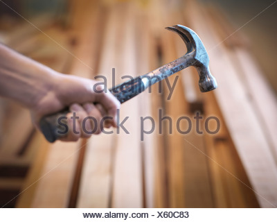 Hand holding hammer next to timber - Stock Photo