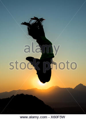 Silhouette Woman Jumping Against Clear Sky During Sunset - Stock Photo