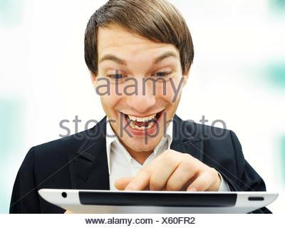 Businessman working on an iPad, focused, happy, portrait - Stock Photo