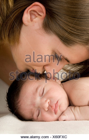 Mother kissing her sleeping newborn baby, two weeks old - Stock Photo