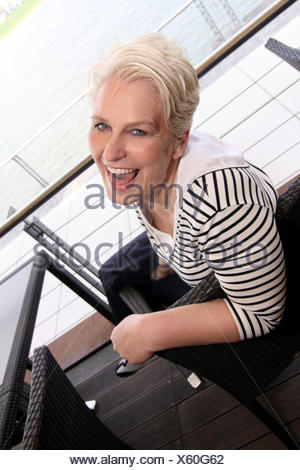 attractive white-haired woman turning around in a cafe chair laughing at the camera, Germany, North Rhine-Westphalia, Agrippinawerft, Cologne - Stock Photo