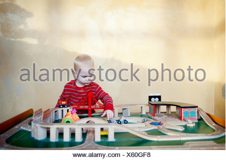 Young boy playing with toy train set - Stock Photo