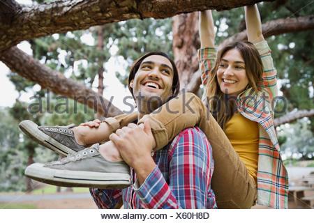 Happy young man supporting woman hanging on tree branch in park - Stock Photo