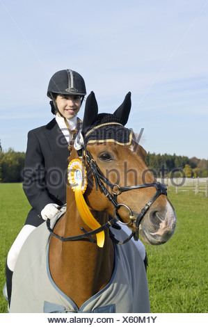 Girl on back of German pony, winner of competition - Stock Photo