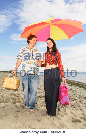 Couple strolling along the beach - Stock Photo
