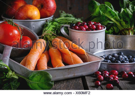 Assortment of fresh fruits, vegetables and berries. Bunch of carrots, spinach, tomatoes and red apples, blueberries and cranberr - Stock Photo