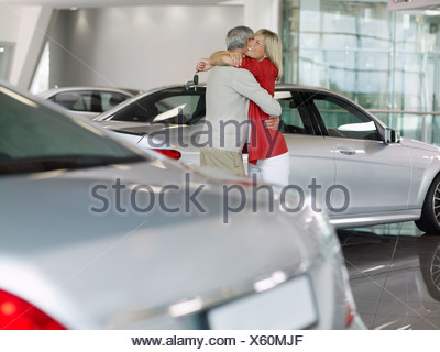 Happy couple hugging in automobile showroom - Stock Photo