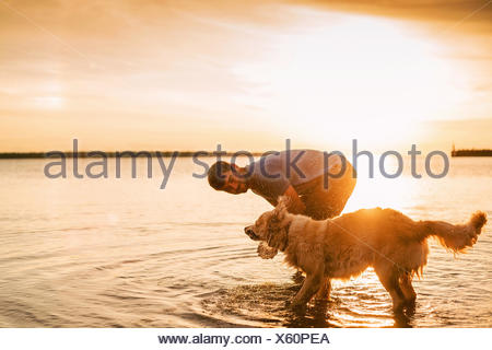 Man playing with his golden retriever dog in lake at sunset - Stock Photo