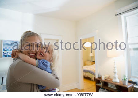 Portrait enthusiastic mother and daughter hugging - Stock Photo