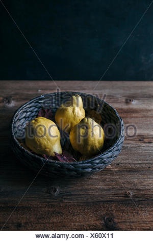 Quince in basket on rustic wooden table - Stock Photo